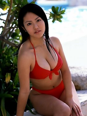 A tight skimpy red bikini holds in this idols big busty boobs